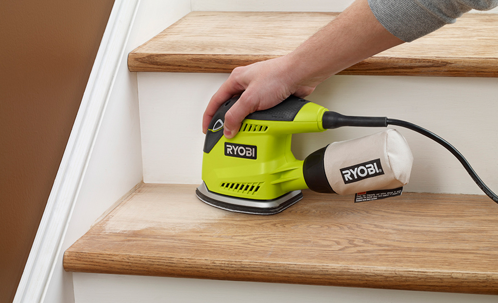A person uses an orbital sander on a wooden step.