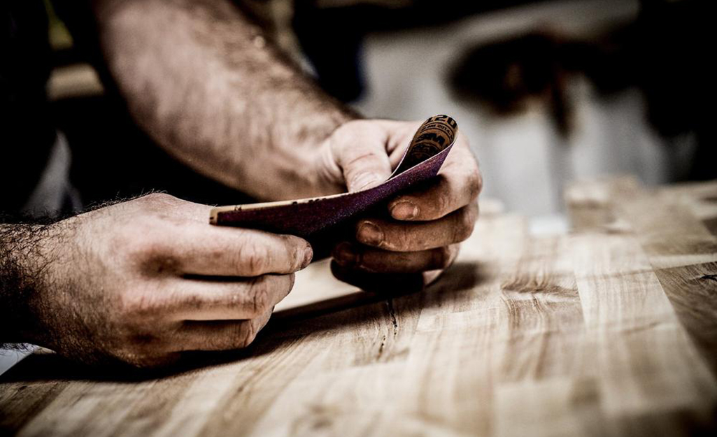 A person folds a piece of ceramic sandpaper before sanding wood.