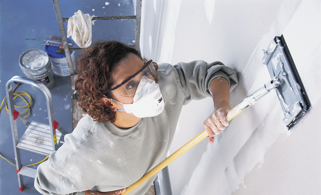 A person uses a drywall sanding pad and an extension pole.