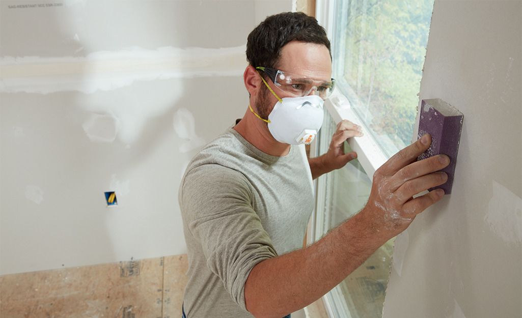 A person sands a wall with a sanding block.