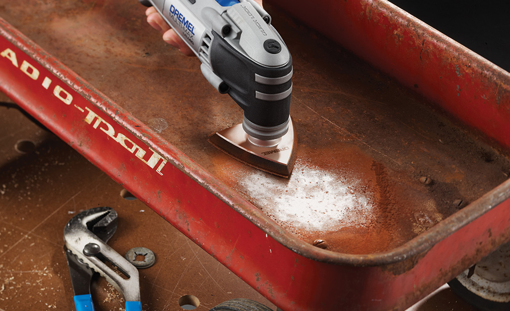 A person uses a sander on a rusty metal wagon.