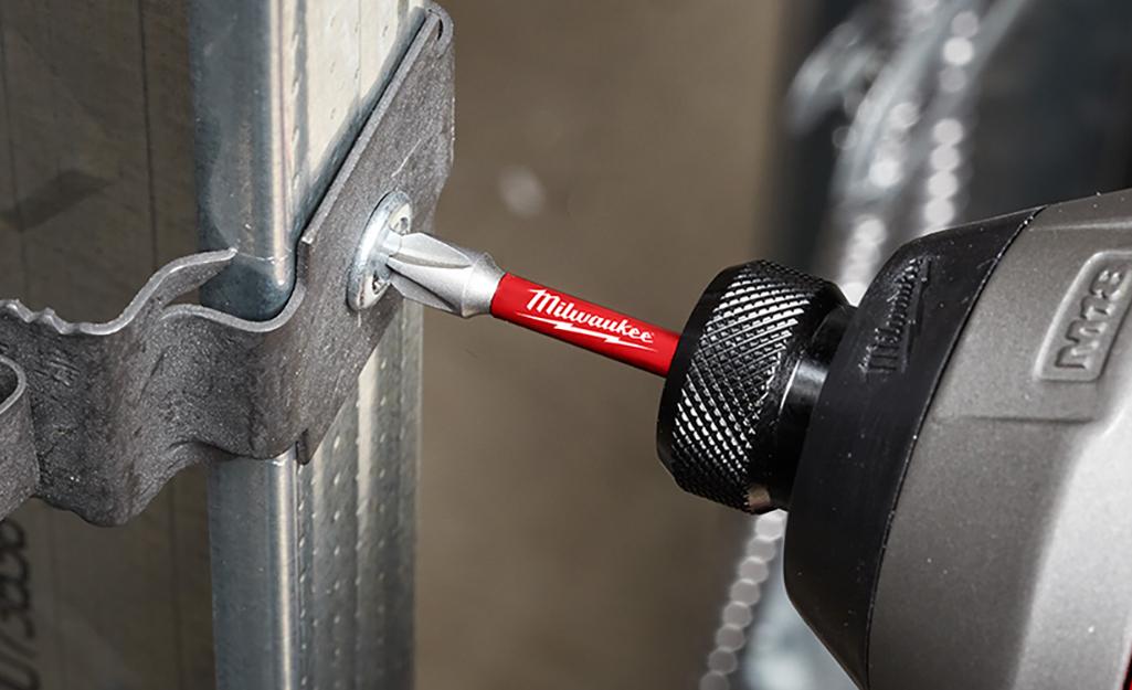 A Security T power screwdriver attaches a metal bracket.