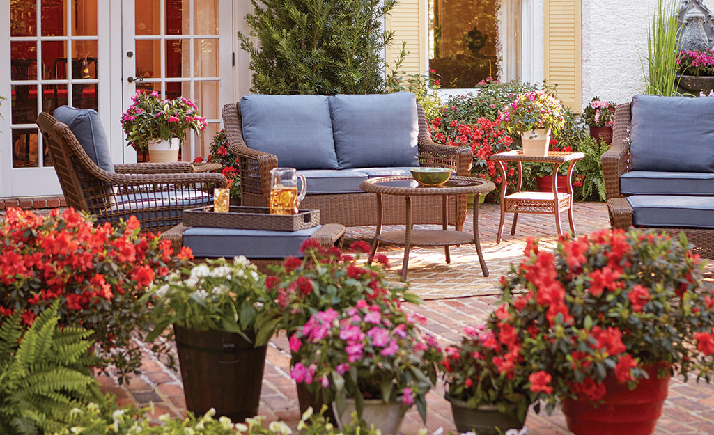 Pots of spring flowers on a patio with a love seat and chairs with blue cushions.