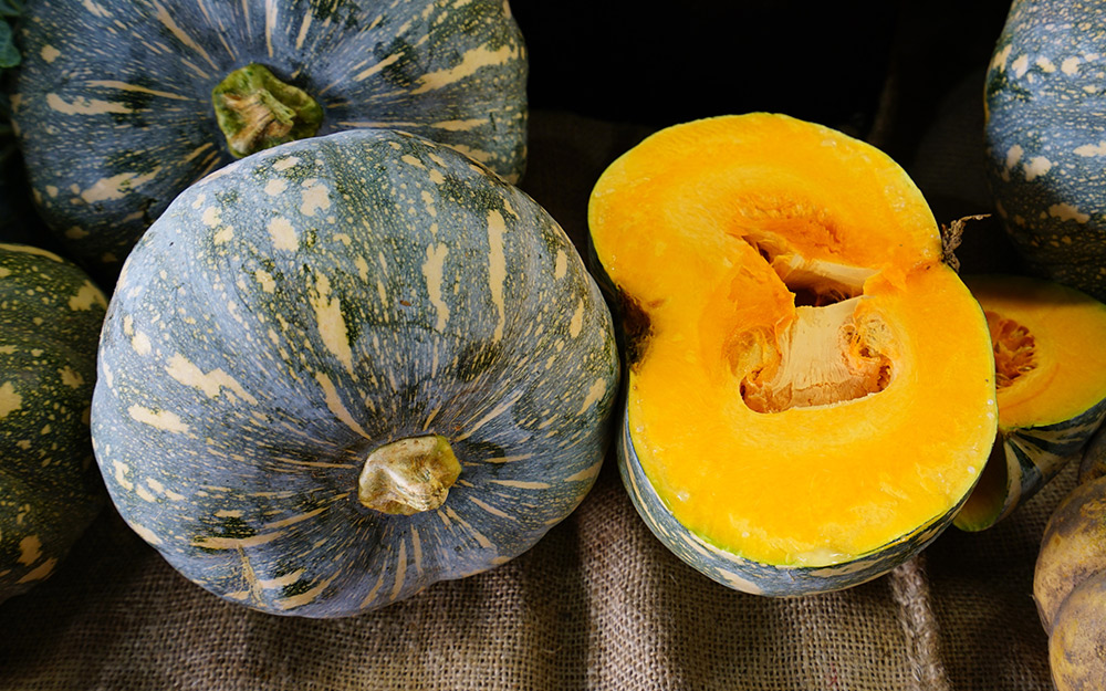Kabocha squash with one sliced open on a table.