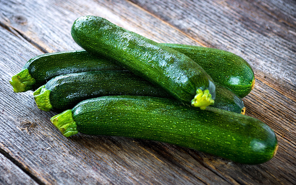 A pile of zucchini on a wooden table.