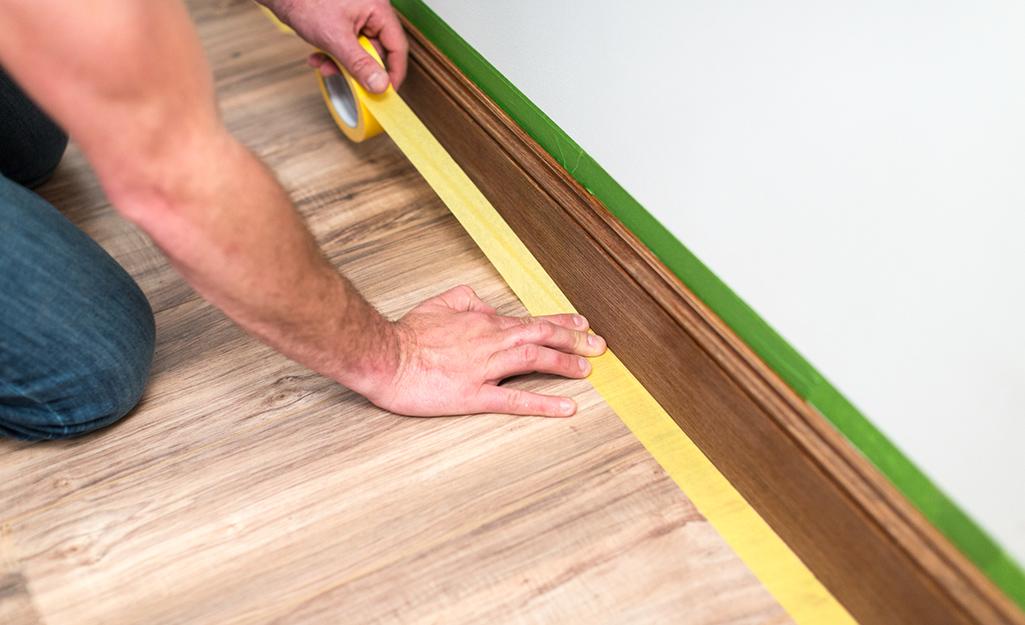 A person applies masking tape along a baseboard.