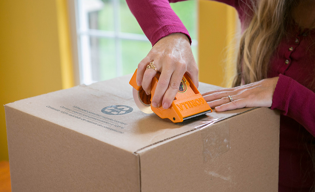 A person uses packing tape to seal a box.