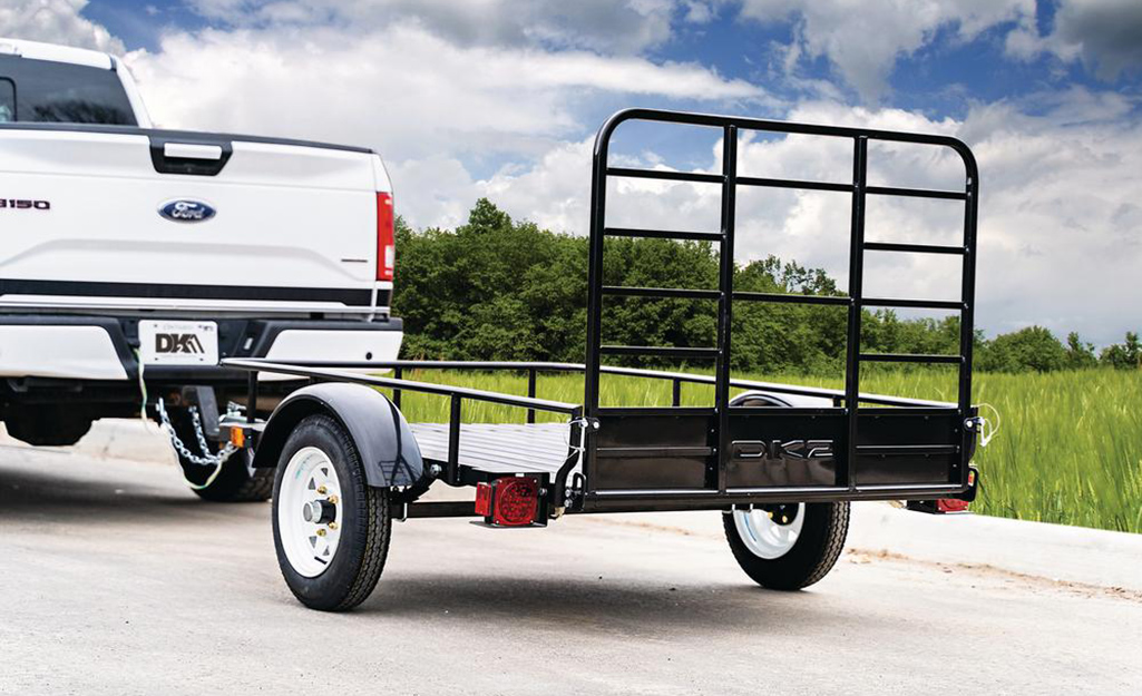A utility trailer attached to the back of a truck.