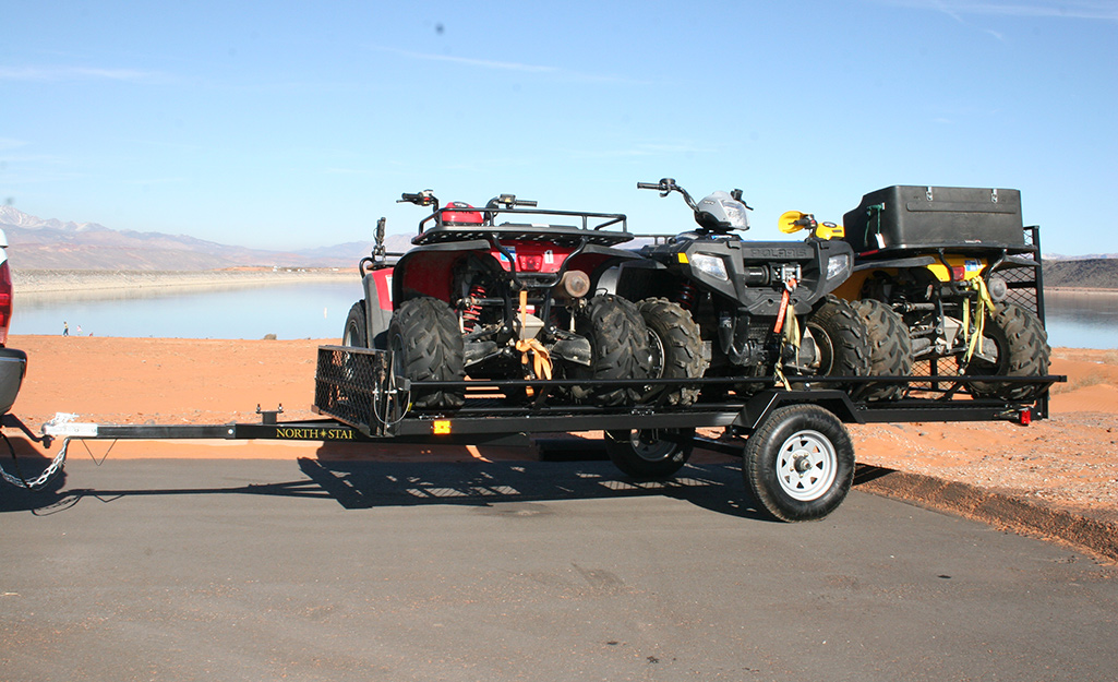 A utility trailer hauling four-wheelers.