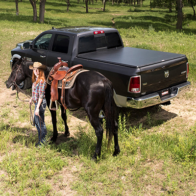 A woman an a horse standing in a field next to a truck with a bed cover