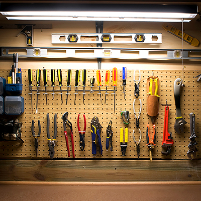 Tube lights hang over tools on a pegboard in a workshop.