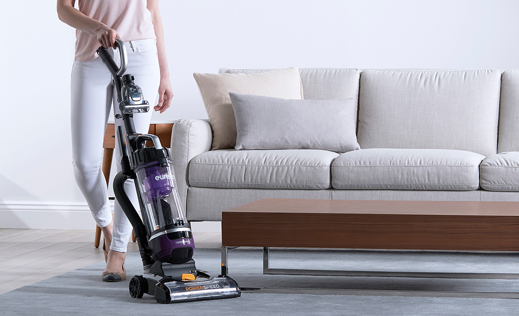 A person vacuuming in front of a sofa with an upright vacuum cleaner.