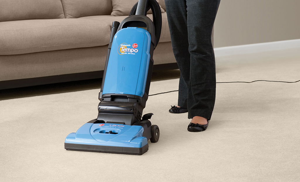 A person pushing an upright vacuum cleaner along the carpet.