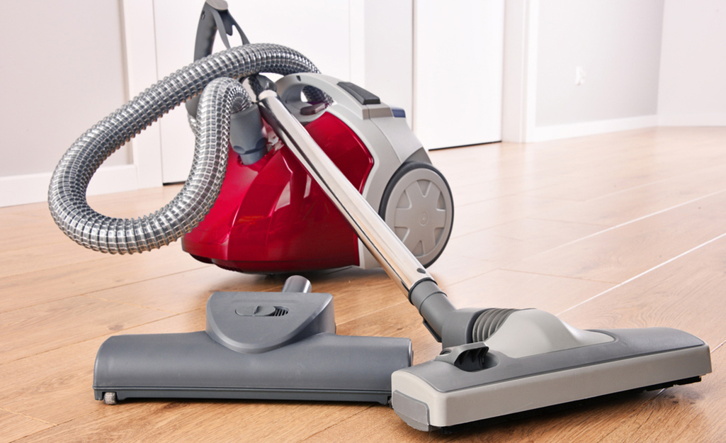 A canister vacuum atop hardwood floors.