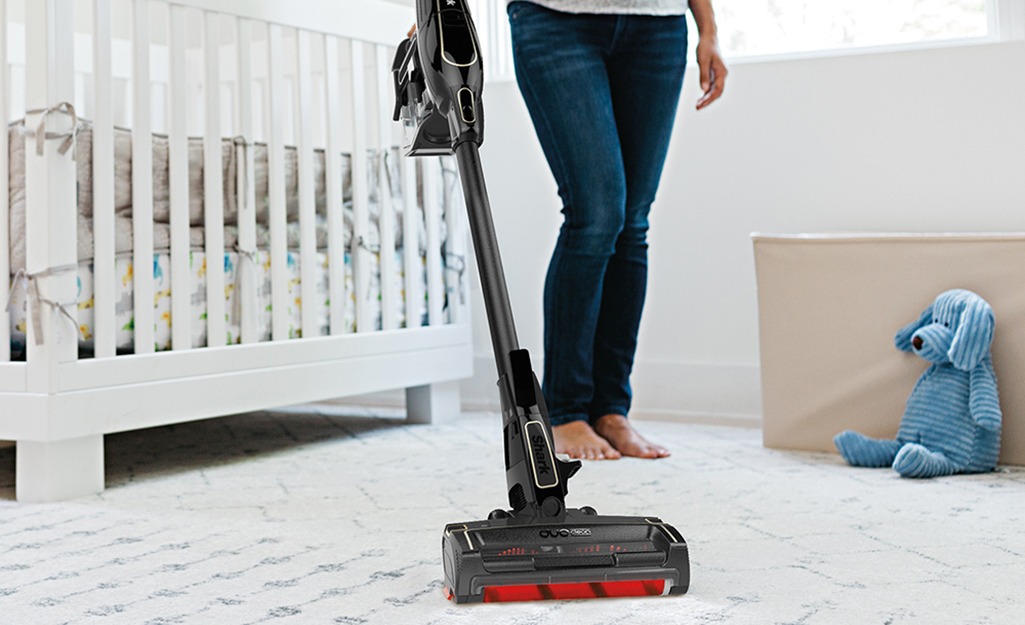 A person pushing a cordless stick vacuum cleaner along a nursery carpet.