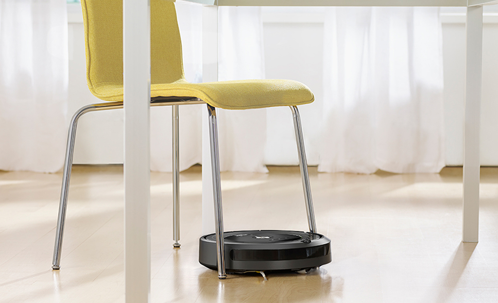 A robotic vacuum atop hardwood floors.