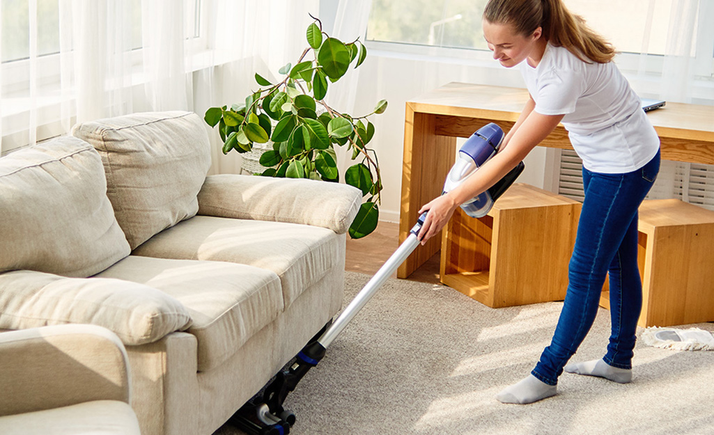 A person pushing a vacuum cleaner along the carpet under a sofa.