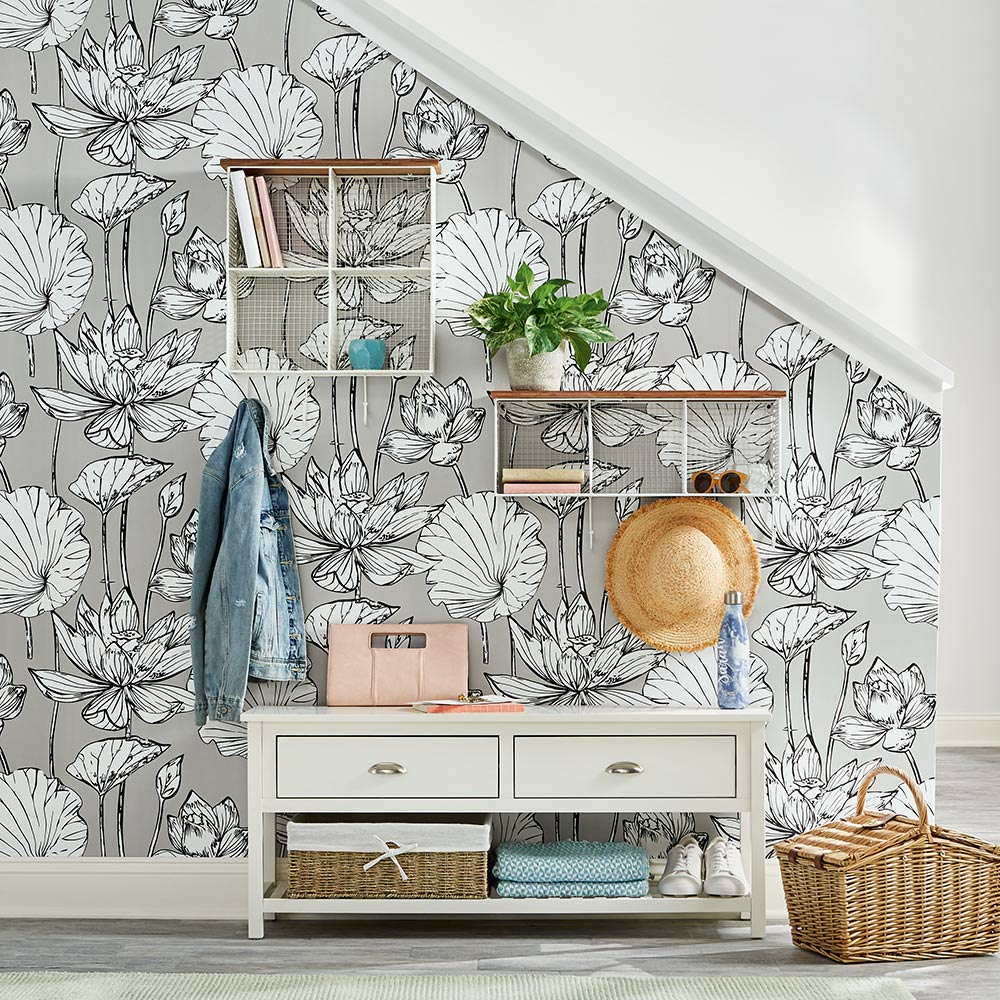 An entryway with flower patterned wallpaper.