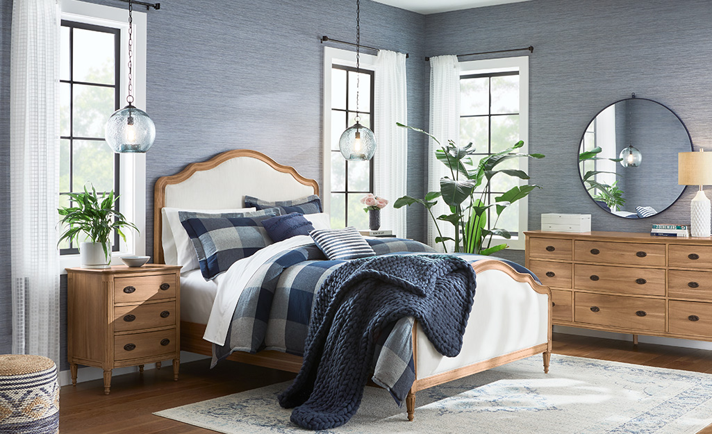 A bedroom with grayish blue wallpaper.