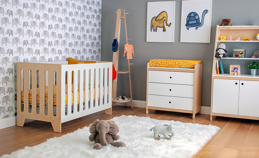 A children's nursery with elephant patterned wallpaper