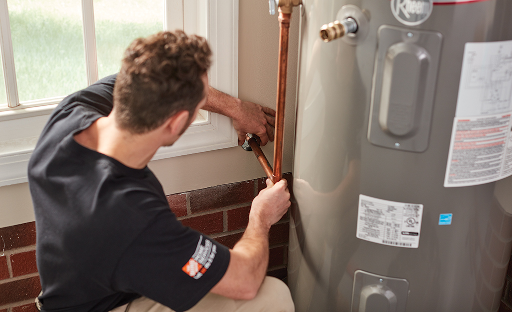 A person installing a tank water heater.