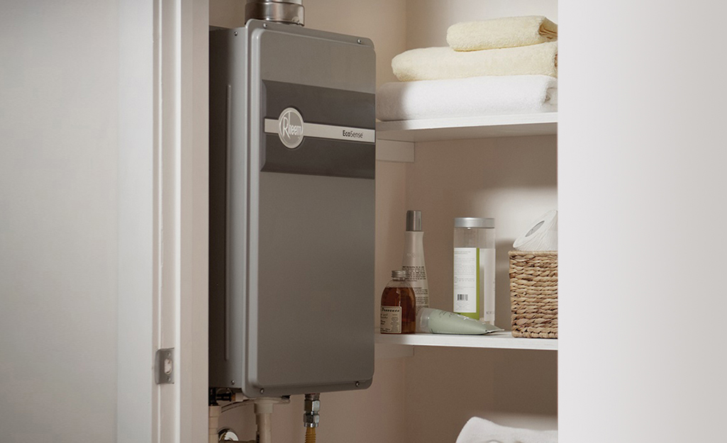 A tankless water heater installed on a wall near a storage closet