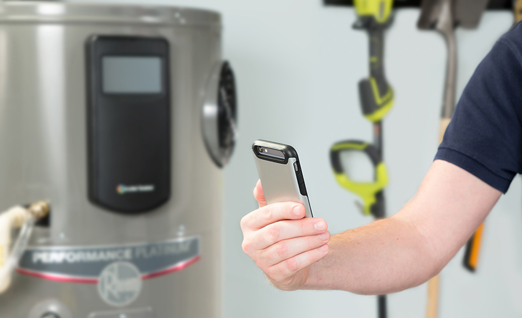 A person programs a smart water heater from a cell phone.