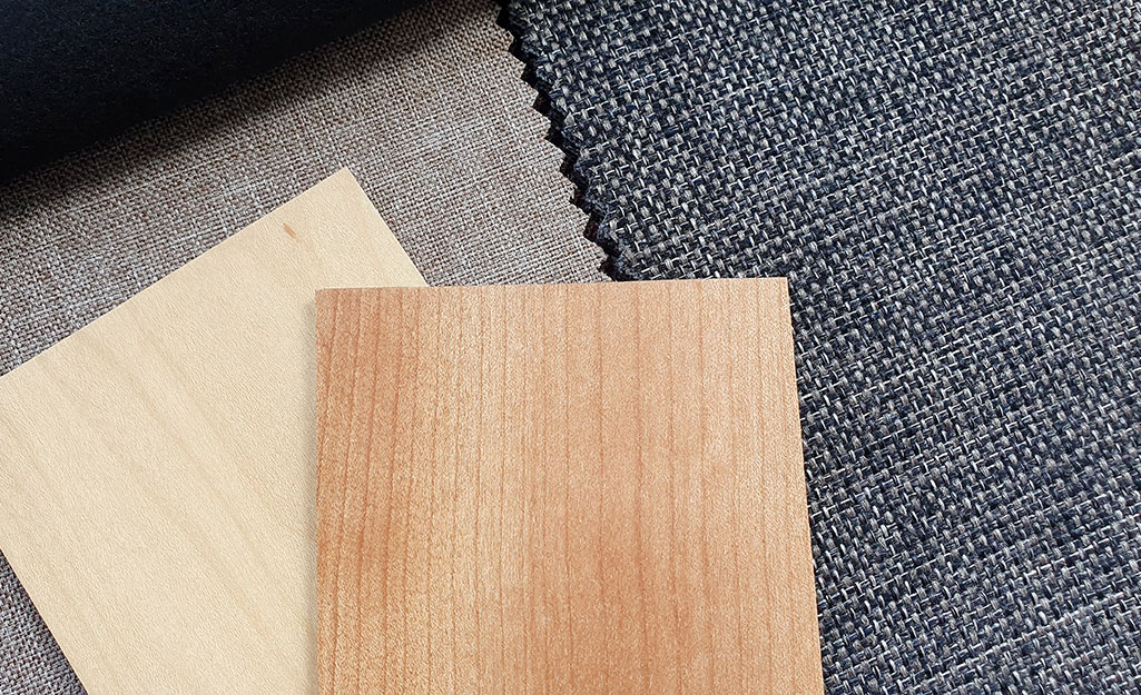 Wood, fabric and plastic window treatments spread out on a table.