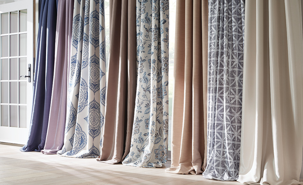 Draperies in different prints hanging by a door.