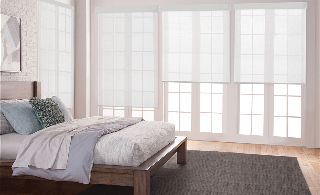 White roller shades installed in a bedroom.