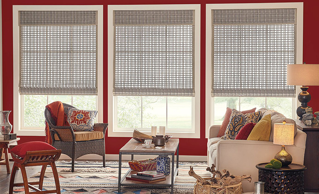 Woven window shades hanging in a red room.