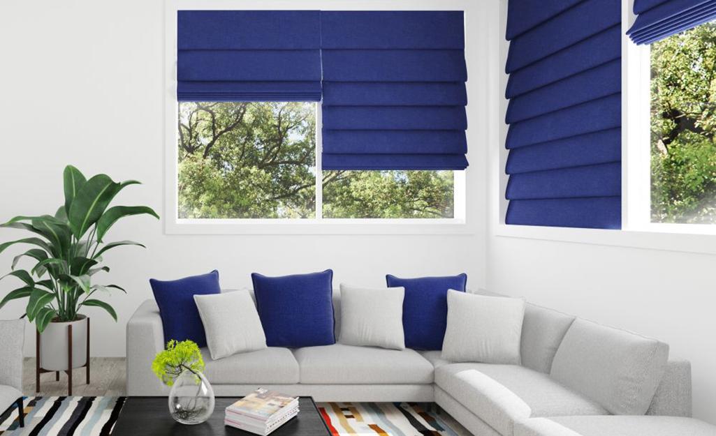 Blue Roman shades hanging in sunroom windows.