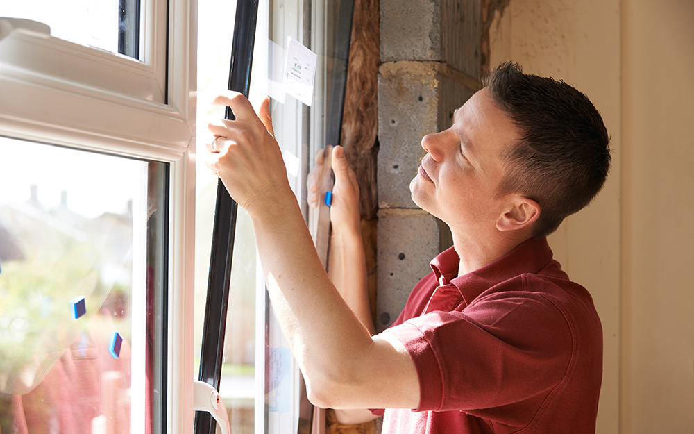 man in red shirt installing a window