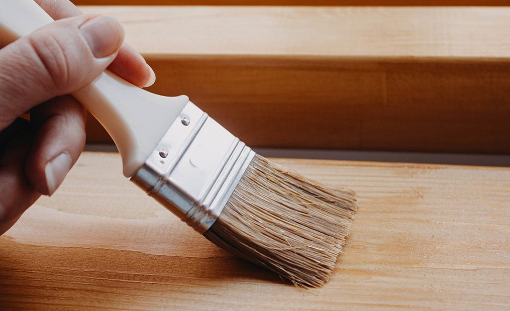A person applies wood finish to a wood surface with a paint brush.