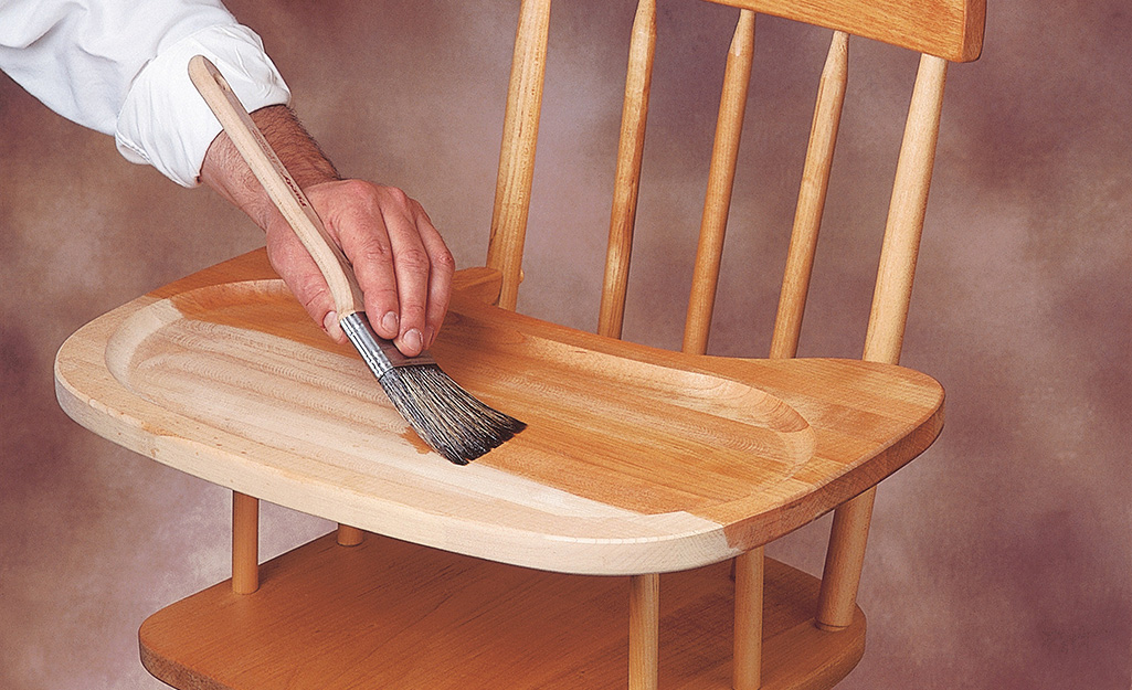 A person coats a high chair with shellac wood finish.