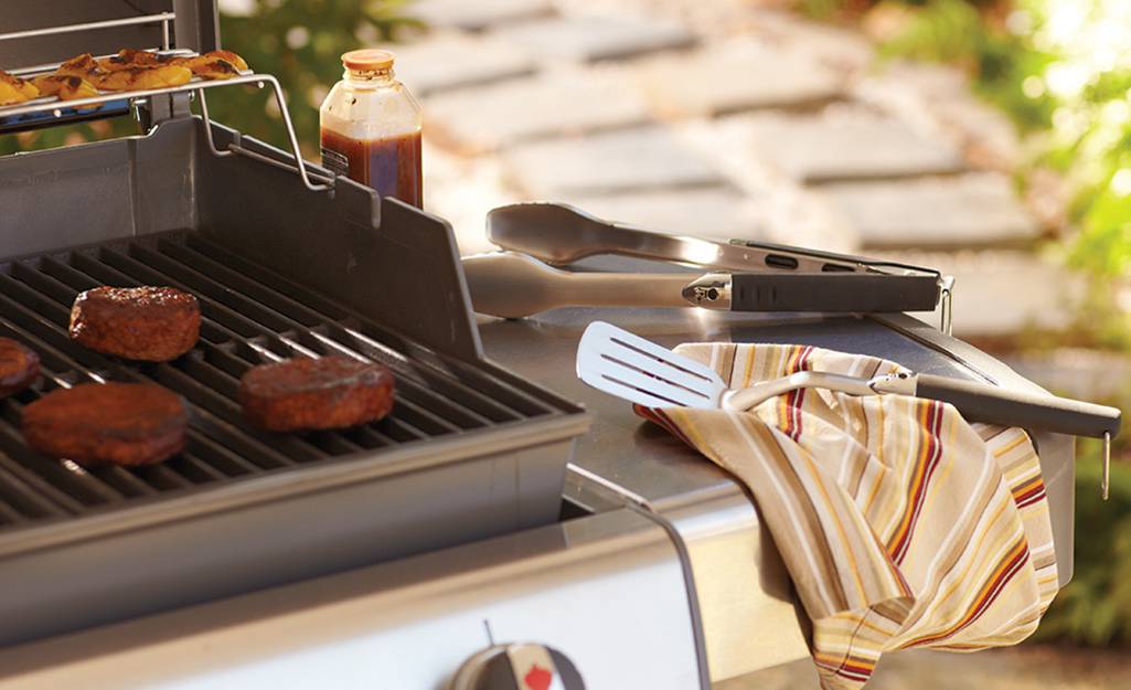 A spatula and tongs resting on a grill's side shelf.