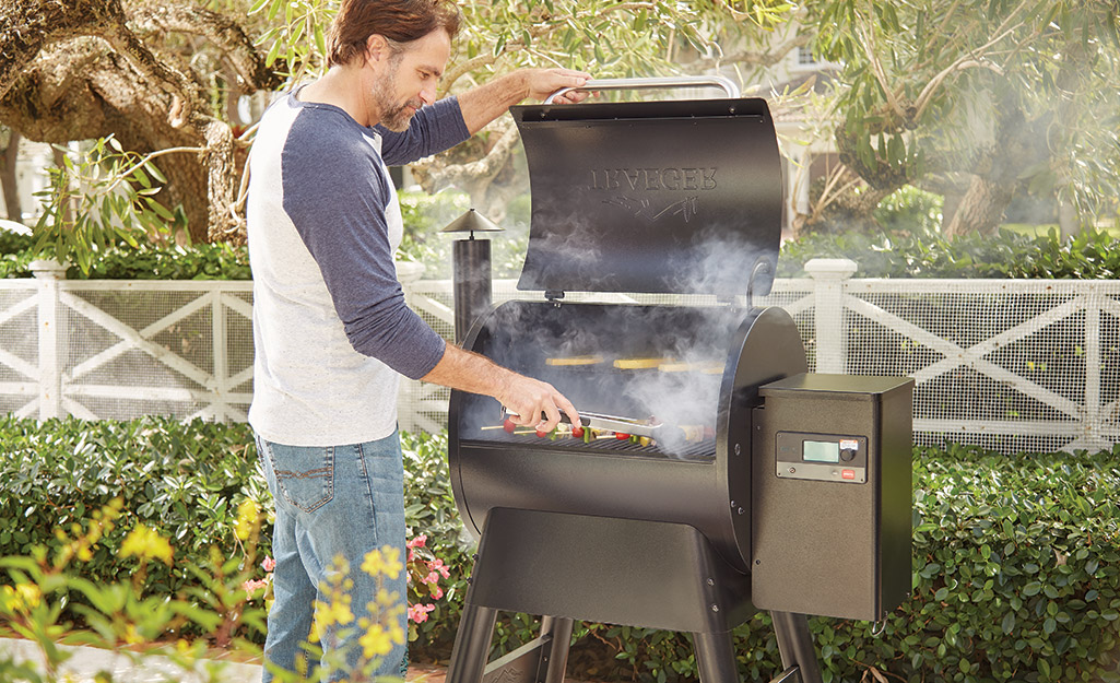 A person tending to food cooking on a pellet grill.