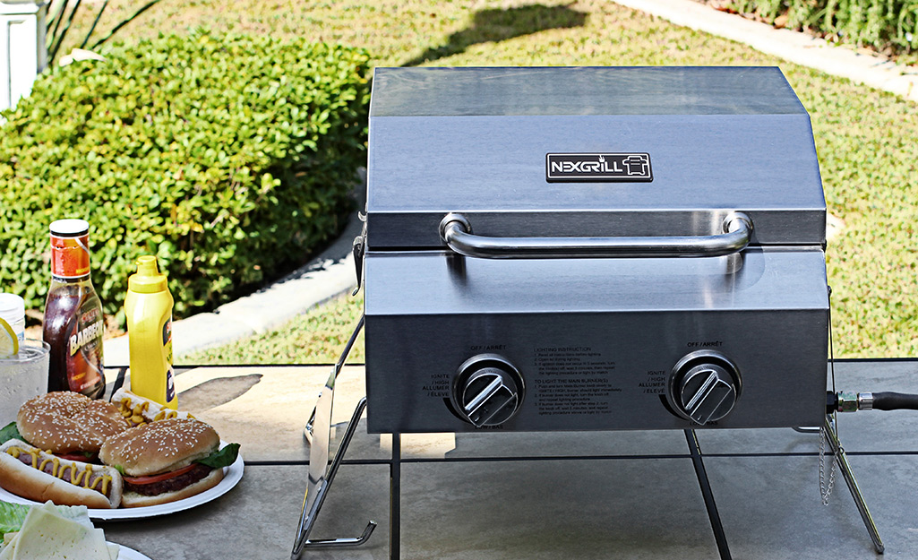A portable grill sitting on a table on a patio.