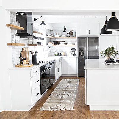 A kitchen with hardwood floors, white cabinetry, and black accents.