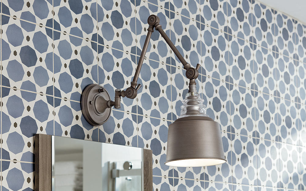 Bath vanity lighting with a dark metal finish against a cool blue painted wall.