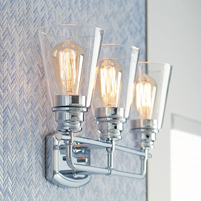 Sconce lighting hanging in a blue tiled bathroom with a blue bath vanity.