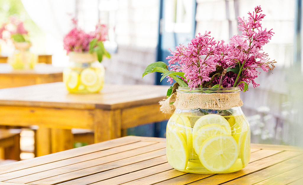 Vase filled with lemon slices in water with pink flowers.