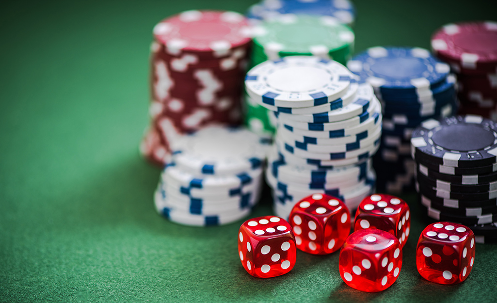 Stacks of poker chips and dice on a green cloth.