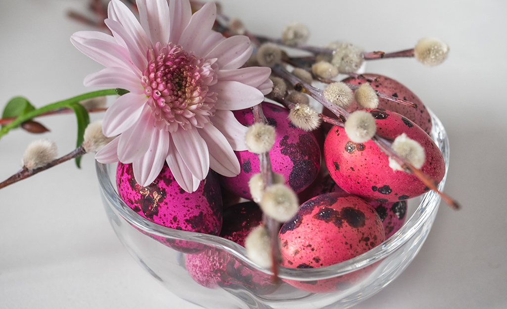 Vase filled with pink bird eggs and flowers.