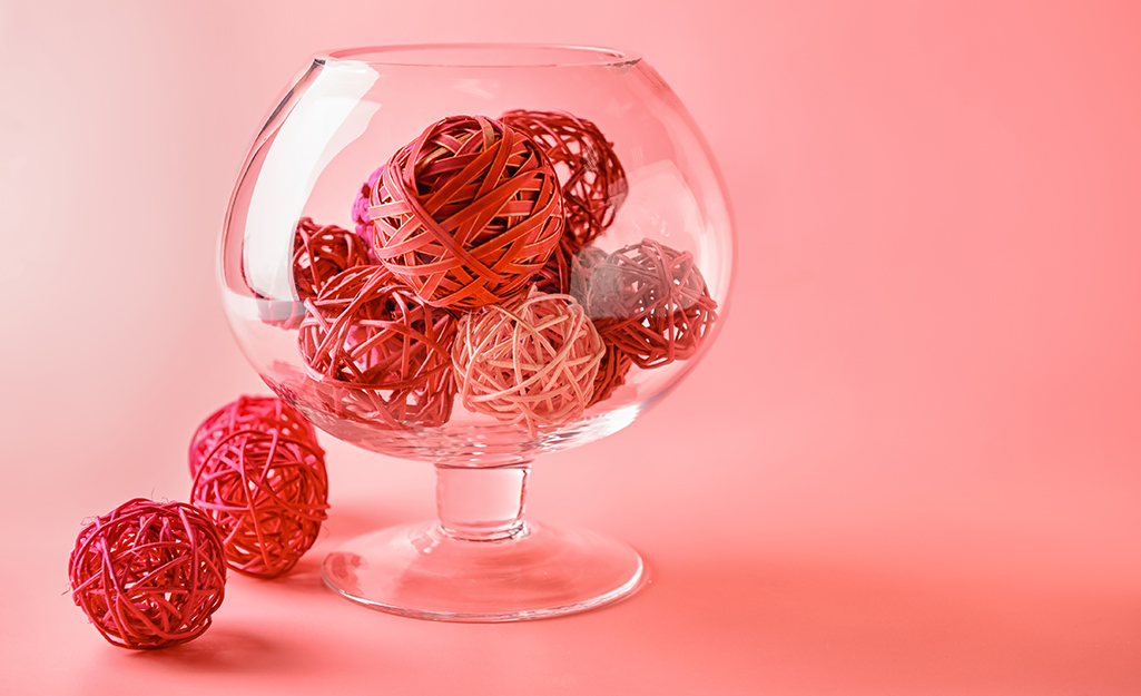 Brandy sniffer vase filled with red and pink vine balls.