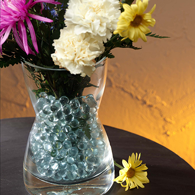 Vase filled with glass beads and flowers.