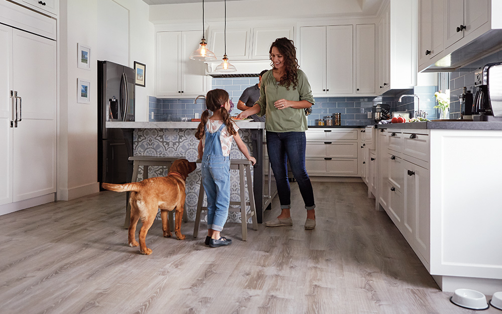 A mom, child and the family dog enjoying a durable, beautiful vinyl floor in the kitchen.