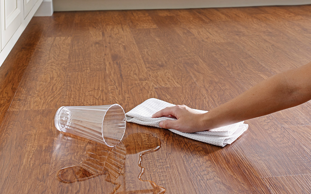 Someone easily wiping up a water spill with a towel on an easy-care vinyl floor.