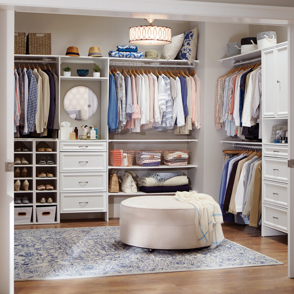 Shirts hang from rods in a large walk-in closet that also includes shelves and drawers for storage.