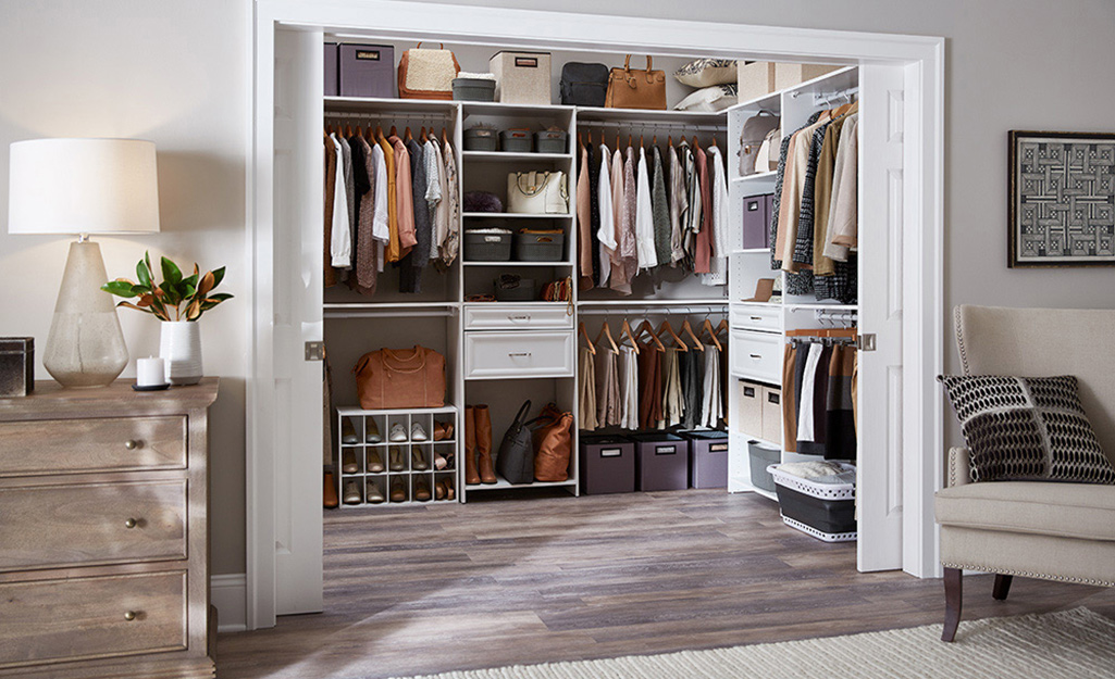 The doors to large walk-in closet stand open to show an organized closet system than includes rods, drawers and shelves.